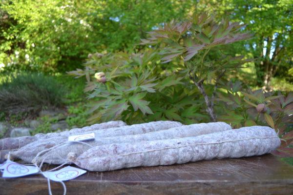 Quattro salami della rosa su tagliere con piante sullo sfondo- Agrisalumeria del Bosco