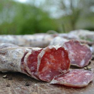 Salsiccia stagionata su tagliere con grani di pepe- Agrisalumeria del Bosco